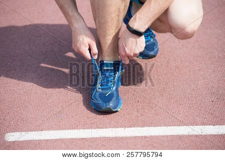 Getting Ready To Jogging. Hands Tying Shoelaces Sneaker Running Track Background. Hands Of Sportsman