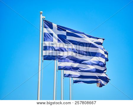 Four Official Flags Of Greece Waving On A Blue Sky.