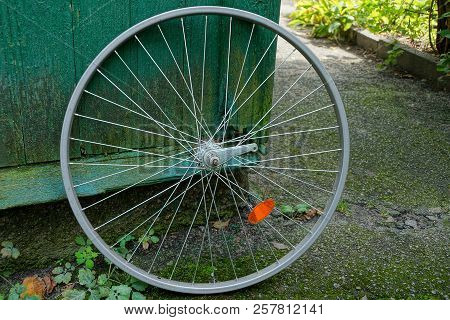 Gray Iron Rim Of A Bicycle Wheel Near A Green Wooden Wall In The Street