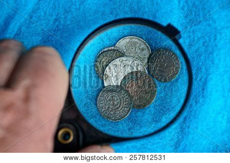 Old Silver And Copper Coins In A Pile Under A Magnifying Glass On A Blue Woolen Fabric