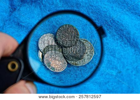 Old Silver And Copper Coins Under A Magnifying Glass On A Blue Woolen Fabric