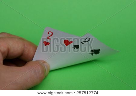 Two Playing Cards In Fingers Of Hands On A Green Background