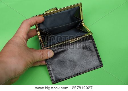 Open Brown Empty Purse In Hand On A Green Background