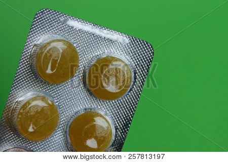 One Gray Blister With Round Yellow Pills On A Green Background