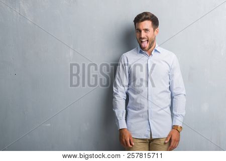 Handsome young business man over grey grunge wall wearing elegant shirt sticking tongue out happy with funny expression. Emotion concept.
