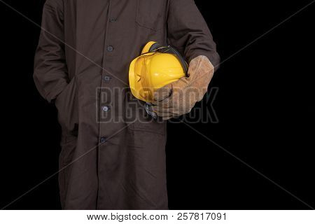 Worker With A Helmet In His Hand Wearing A Protective Apron. Health Protection Of Production Workers