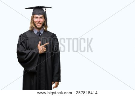 Young handsome graduated man with long hair over isolated background cheerful with a smile of face pointing with hand and finger up to the side with happy and natural expression on face