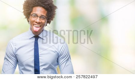 Afro american business man wearing glasses over isolated background sticking tongue out happy with funny expression. Emotion concept.