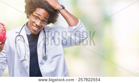 Afro american cardiologist doctor man over isolated background stressed with hand on head, shocked with shame and surprise face, angry and frustrated. Fear and upset for mistake.