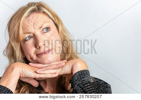 Studio portrait headshot of attractive thoughtful middle aged blond woman in her forties looking up inquisitive or questioning