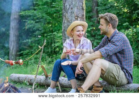 Winner Eats First. Couple Tourists Throwing Their Gesture While Sit Log Near Bonfire. Man And Girl P