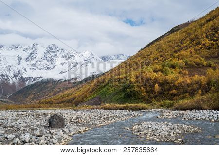 Zemo Svaneti autumn. Enguri river and Shhara mountain, Georgia. Landscape with Main Caucasian ridge