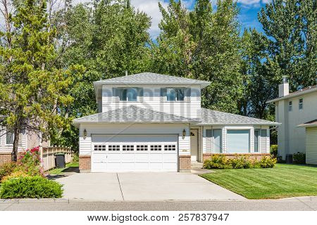A Perfect Neighbourhood. Family House With Landscaped Front Yard And Concrete Driveway. Residential