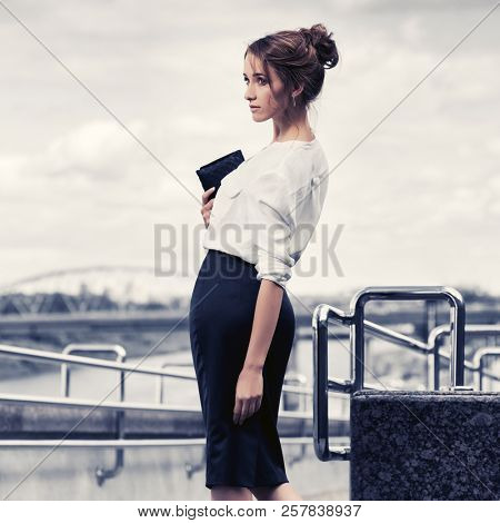 Young business woman with handbag walking in city street Stylish fashion model with bun updo hair wearing white shirt and pencil skirt