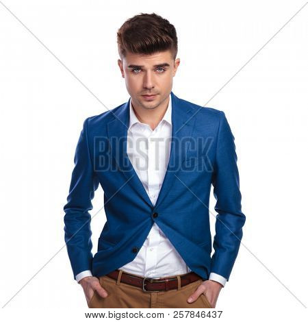 handsome elegant man with hands in pockets looks at the camera on white background