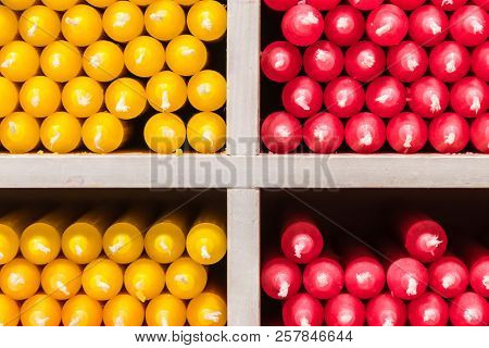 Red and yellow paraffin stick candles arranged on shelves in a shop poster