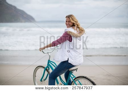 Smiling mature woman riding bicycle on the beach