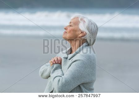 Senior woman doing meditation on the beach