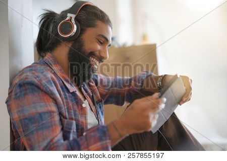 Hipster guy sitting on floor, listening to music on tablet