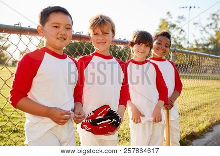 Boys in a baseball team with mitt and bat looking to camera