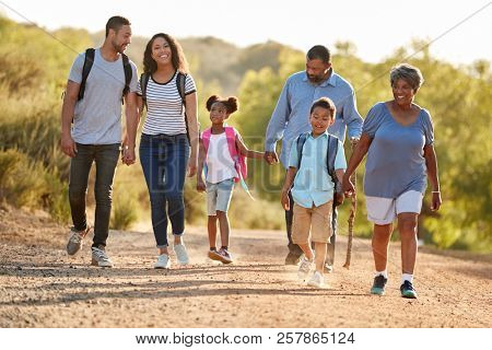 Multi Generation Family Wearing Backpacks Hiking In Countryside Together