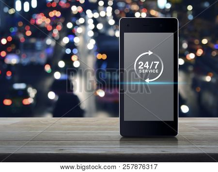 24 Hours Service Flat Icon On Modern Smart Mobile Phone Screen On Wooden Table Over Blur Colorful Ni