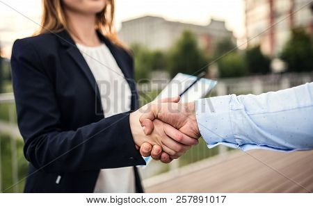 Unrecognizable Young Businessman And Businesswoman Shaking Hands.