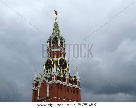 Moscow Kremlin tower on background of dramatic sky with storm dark clouds. Famous Spasskaya tower with chimes before the rain, russian symbol on Red Square poster