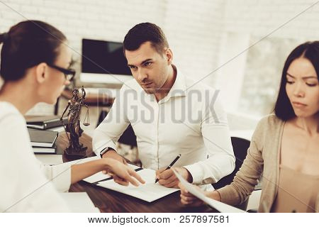 Husband And Wife Signing Document With Lawyer. Young Husband. Problem In Relationship Between People