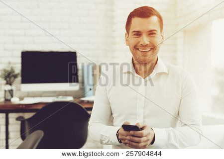 Smiling Young Man With Mobile Phone In Office. Digital Device Computer Desk. Wooden Desk In Office.