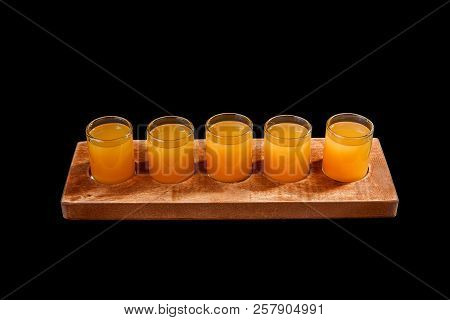 Yellow, same color opaque cocktails, a set of shots in one row, five servings on a wooden stand, substrate. Side view Isolated black background. Drink for the menu restaurant, bar, cafe poster