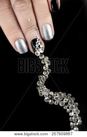 Black silver manicure on short nails with a design of a scattering of rhinestones of different shapes on a black background close-up.Nail art. poster