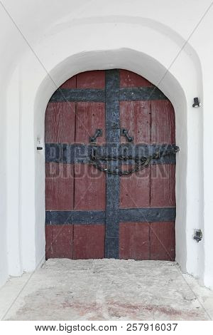 Antique Wooden Door With Wrought Iron Handles And Chain On Whitewashed Wall Background.