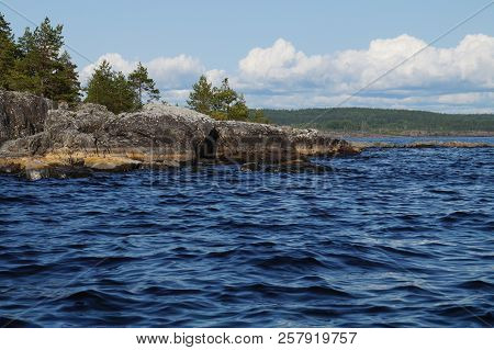 Rocky Shore Of The Lake With Coniferous Trees. Beautiful Water. Far Shore, Overgrown With Forest.