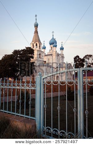 Church Of Peter And Paul In The Village Of Vetvenik With Wrought Iron Gates At Sunset.