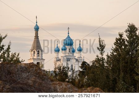 The White-stone Church With Blue Domes Ehind The Rock Against The Evening Sky.
