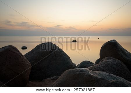 Large Stones On The Background Of The Sea At Sunset Tonted With Orange. Soft Focus.