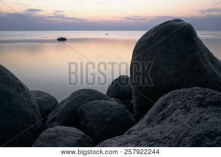 Large Stones On The Background Of The Sea At Sunset Tonted With Purple.