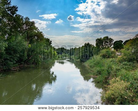 Henares River On Its Way Through The City Of Alcala De Henares In Spain With Very Green Banks And A