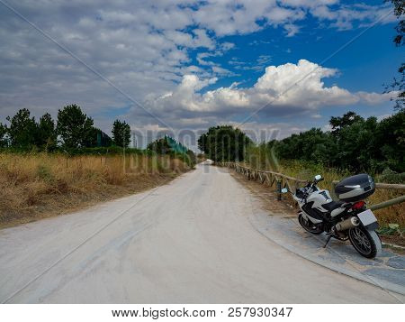 Dirt Road With Dry Yellow Vegetation And Green Trees, With A Motorcycle Parked At The Beginning Of T