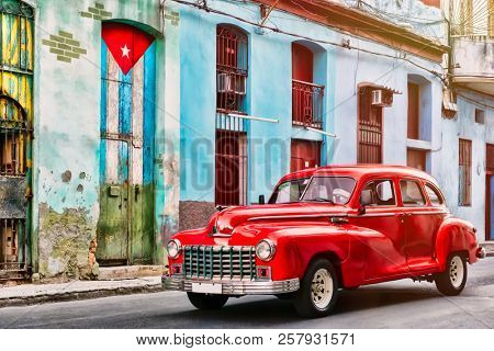 HAVANA,CUBA - SEPTEMBER 5,2018 : Classic car and and old building with the cuban flag in Old Havana