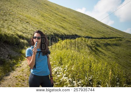 Girl drinking water from her hydration pack in the mountain poster