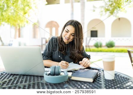 Self-employed Mid Adult Woman Preparing Schedule While Looking At Laptop On Table In Garden