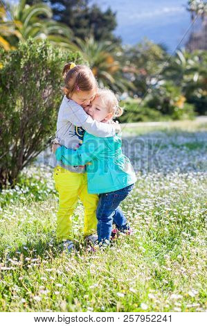 Two Little Girls Are Hugging. Sisters Are On Spring Chamomile Flowers Meadow Near Palms And Mountain