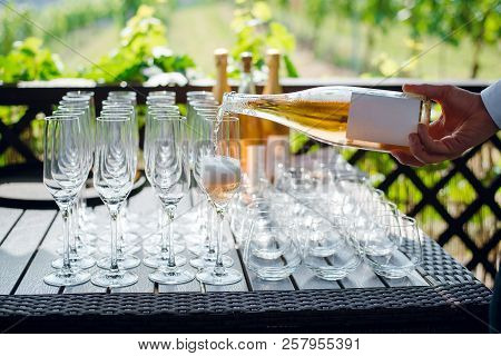 Man Pouring Champagne From A Bottle In Glass. Standing On Buffet Table. Close Up. The Man Filling Th