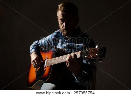 An Old Guitar Player In A Plaid Shirt Plays An Acoustic Guitar. Low Key Portrait.
