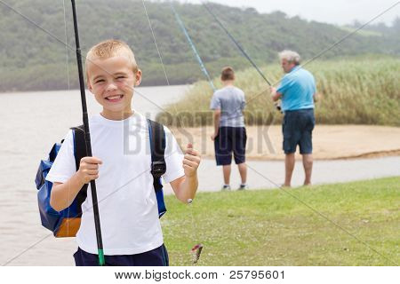 happy little boy fishing with grandpa and brother