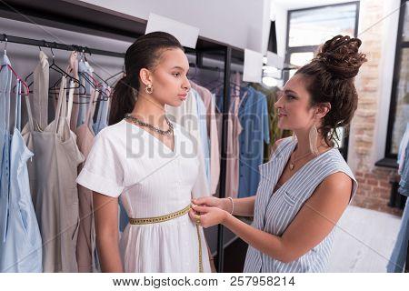 Pleased Female Tailor Mensurating Measurements In Showroom