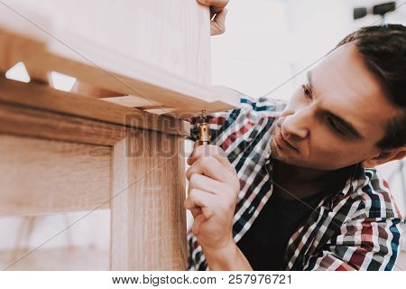 Young Man Assembling Wooden Bookshelf At Home. Wooden Bookcase. Selfmade Furniture. Man And Hobby. W