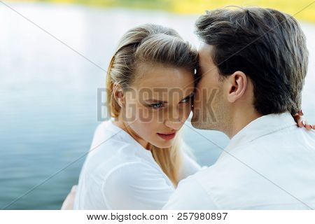 Beautiful Young Woman Being Kissed By Her Husband